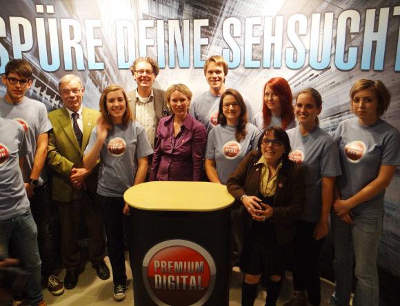 """Dr. Heribert Schlinker, Andreas R. Crüsemann, Ute und Judith Schlinker (v.l.n.r) präsentieren die Kampagne """"Premium Digital"""" im Foyer des Cineplex Warburg im Kreise der Cineplex-Mitarbeiter."""